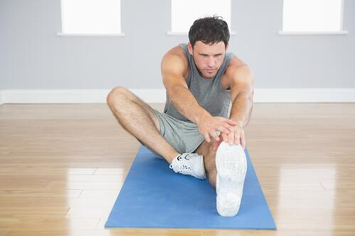 Attractive sporty man stretching his right leg in bright room