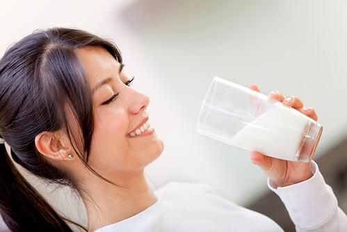 Beautiful woman drinking milk and then smiling