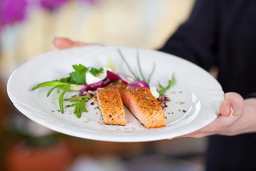 Cropped image of waitress displaying salmon dish in restaurant-3