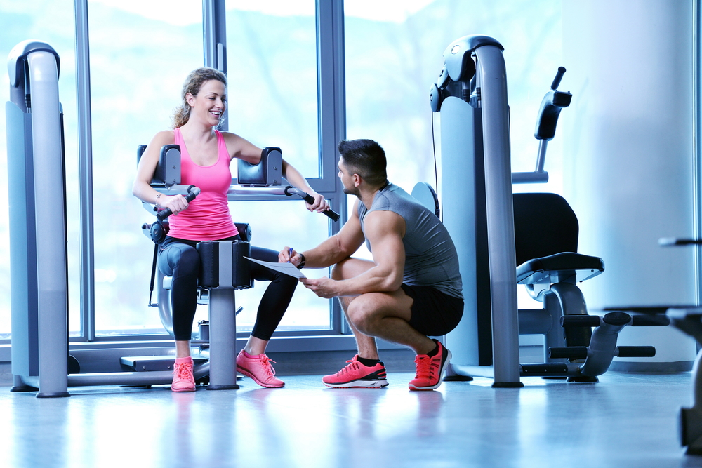 Gym woman exercising with her personal trainer-2