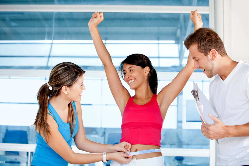 Happy woman at the gym with her trainers measuring her body ? weight loss