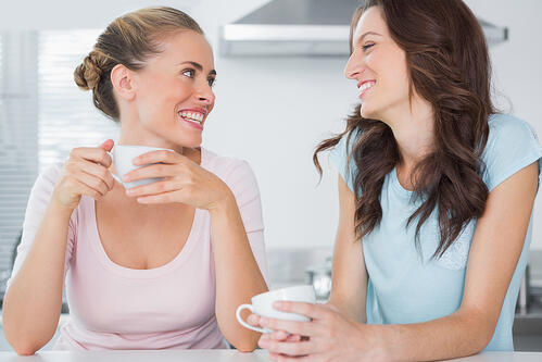 Laughing friends having cup of coffee in the kitchen