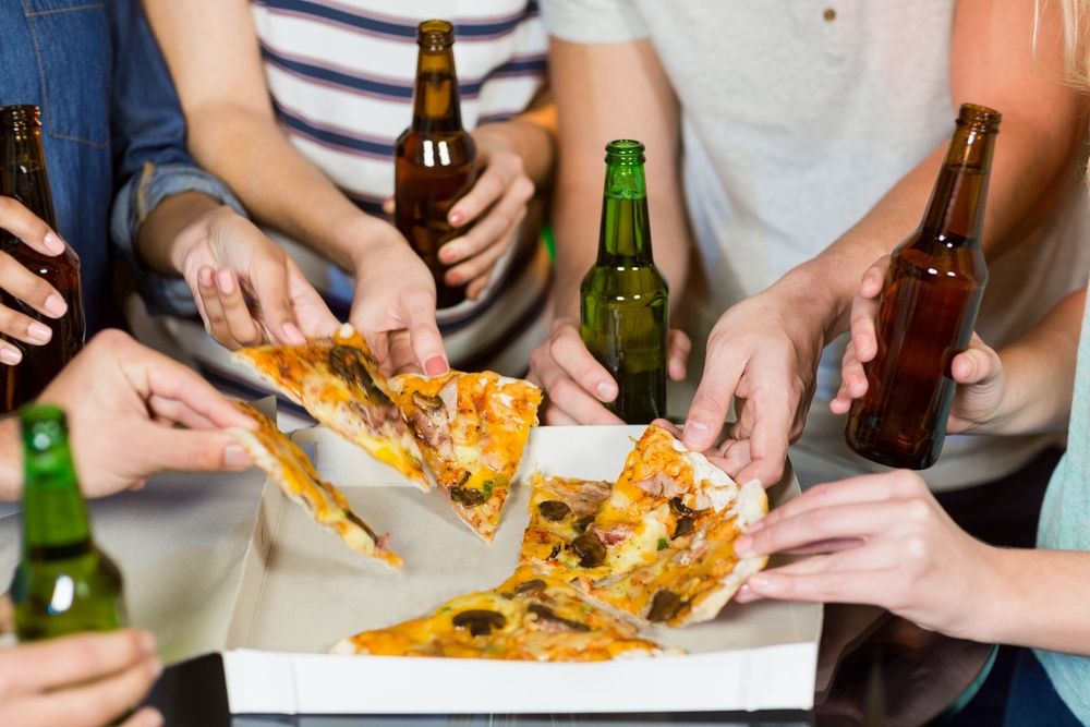 Mid section of friends having bottle of beer and pizza in party at bar-1