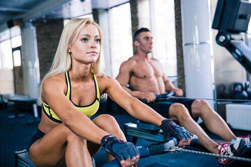 Muscular man and sporty woman workout on training simulator in crossfit gym-1