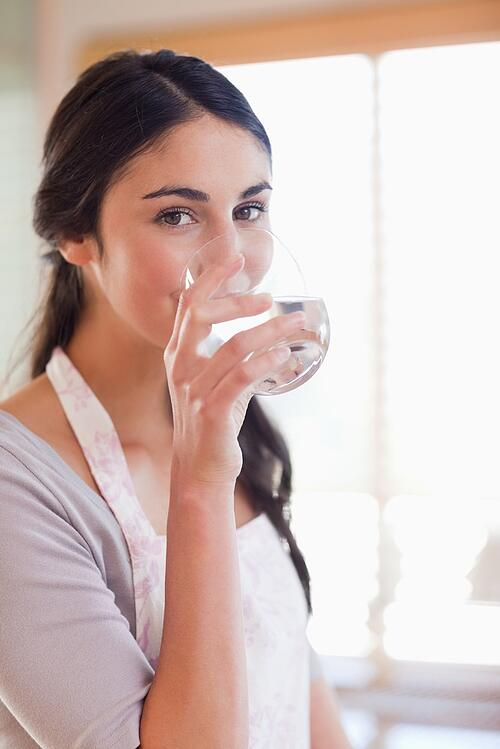 Portrait of a beautiful woman drinking water in her kitchen