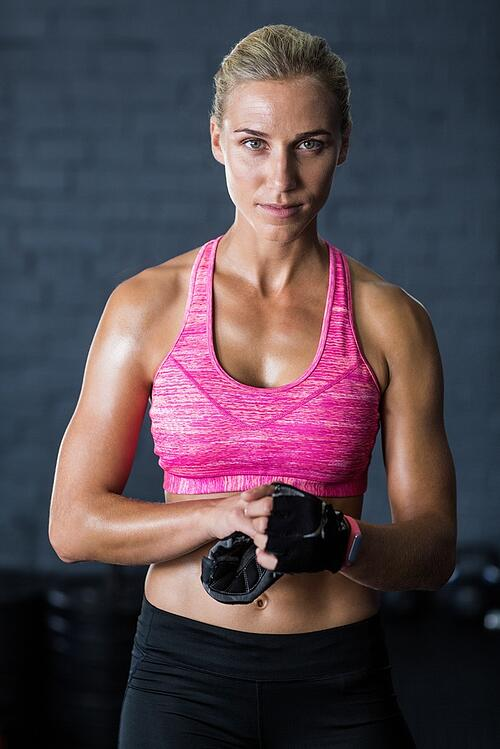 Portrait of pretty athlete removing gloves while standing in gym