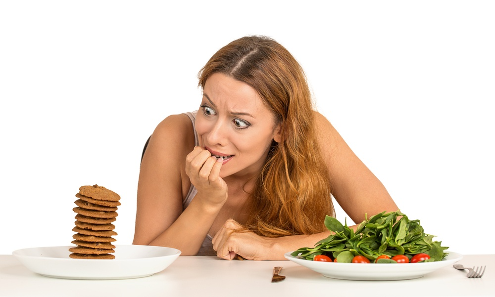 Portrait young woman deciding whether to eat healthy food or sweet cookies she is craving sitting at table isolated white background. Human face expression emotion reaction. Diet nutrition concept