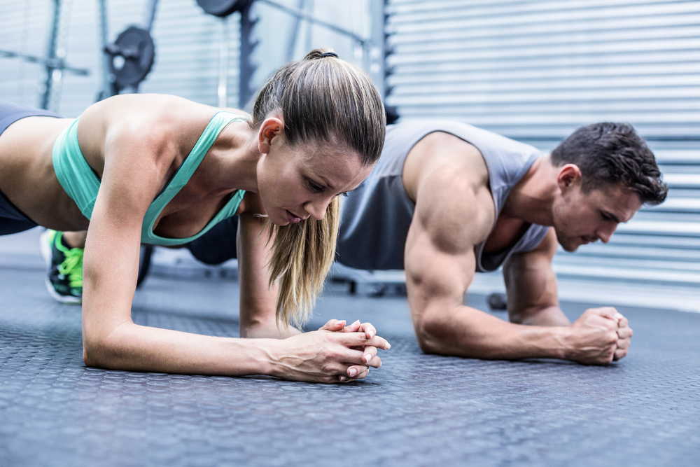 Side view of a muscular couple doing planking exercises-1