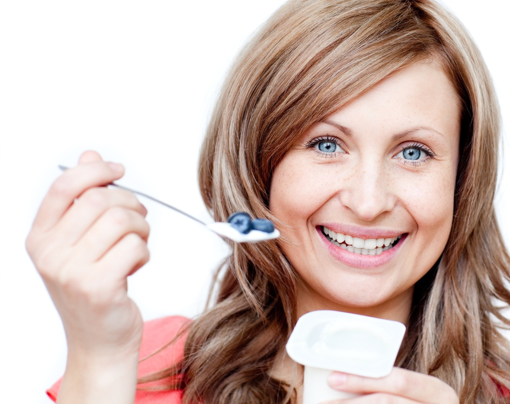 Smiling woman eating a yogurt against a white background