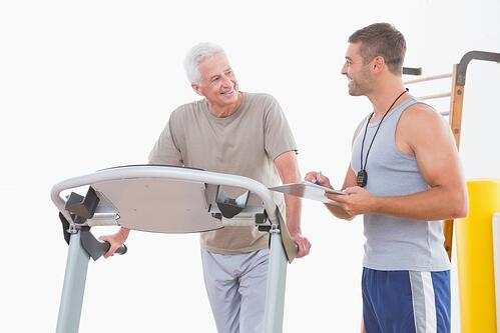 Trainer timing senior man in fitness studio