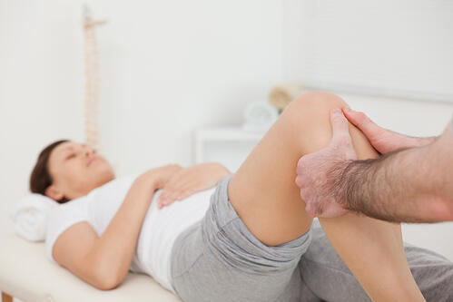 Woman lying while being massaged by her practitioner indoors