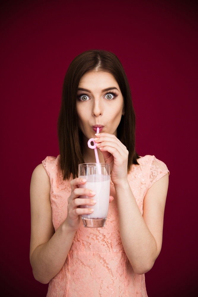 Young pretty woman drinking yogurt over pink background and looking at camera