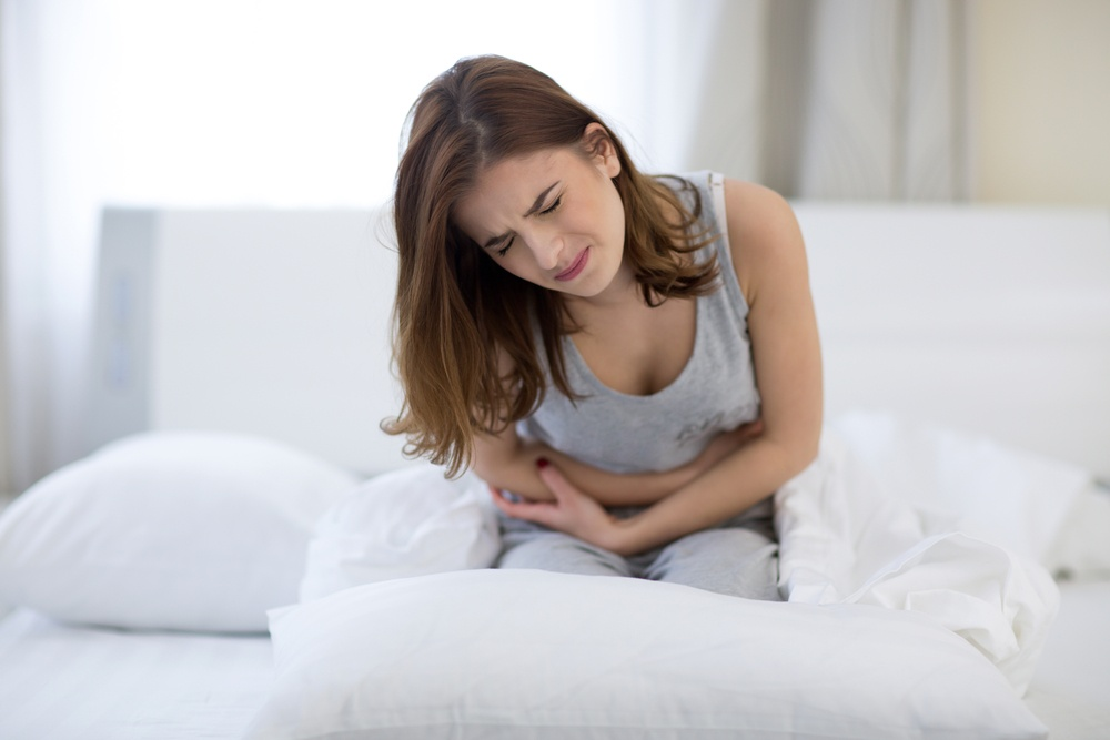 Young woman sitting on the bed with pain-1