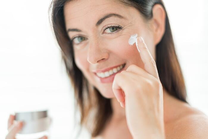 portrait of a beautiful mature lady preventing wrinkles by using a luxurious face lotion