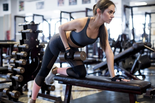 woman-lifting-dumbbell-in-gym_23-2147778563