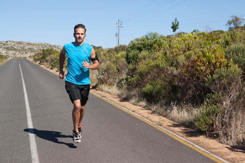 Athletic man jogging on open road on a sunny day
