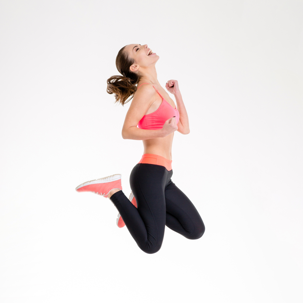 Attractive excited fitness girl in sportwear jumping of joy isolated over white background-1