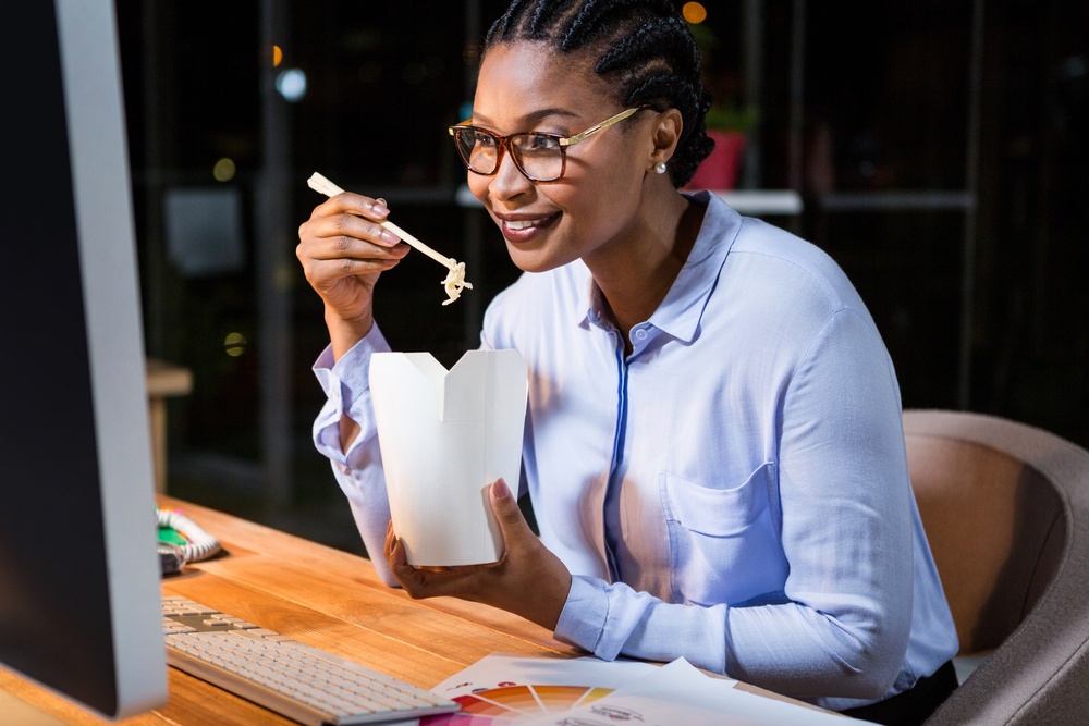 Businesswoman eating noodles at her desk in the office-1