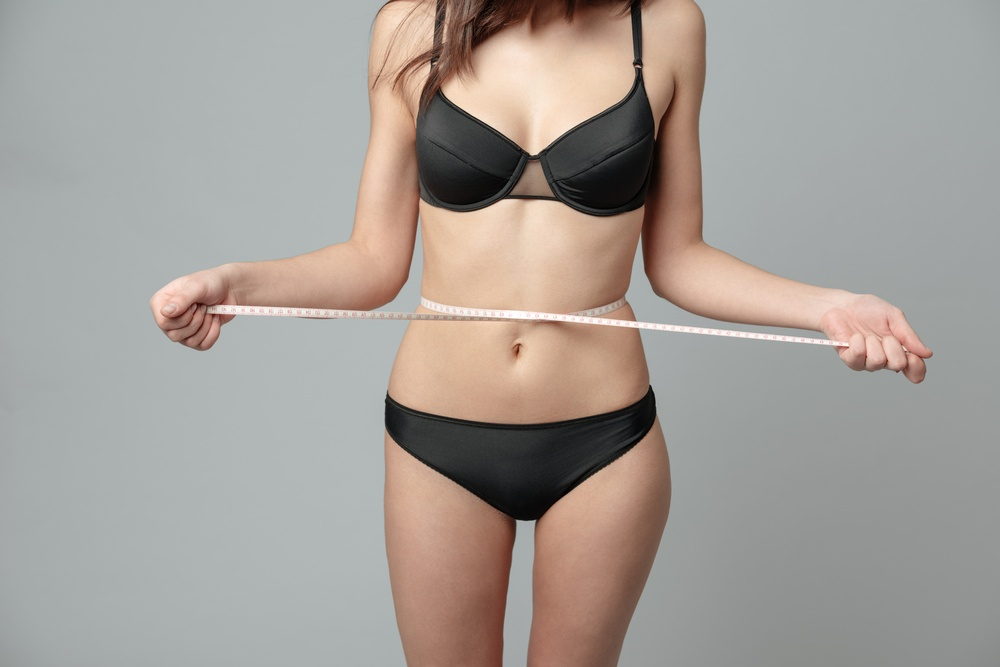 Cropped image of a woman with measuring tape on gray background
