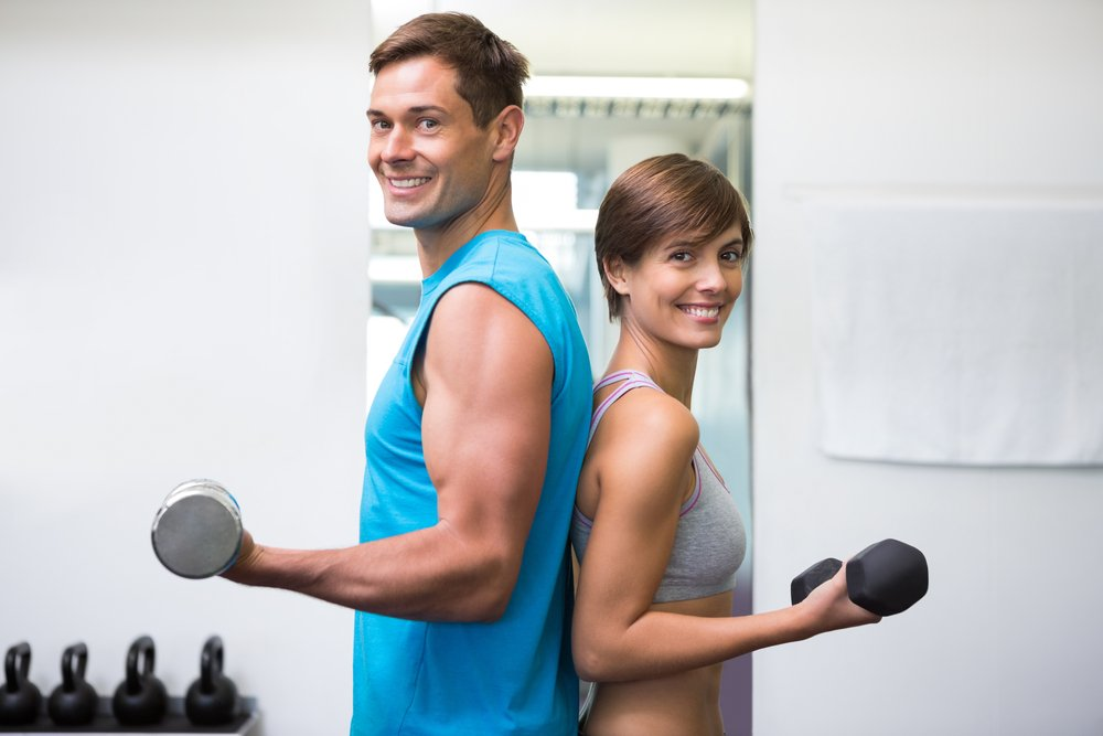 Fit couple lifting dumbbells together smiling at camera at the gym