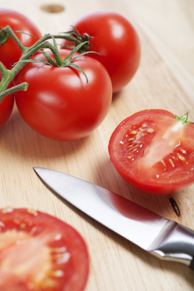 Fresh tomatoes being sliced on a wooden chopping board with knife