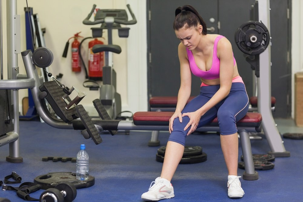 Full length of a healthy young woman with an injured knee sitting in the gym