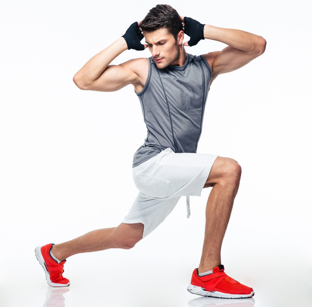 Full length portrait of a fitness man stretching isolated on a white background