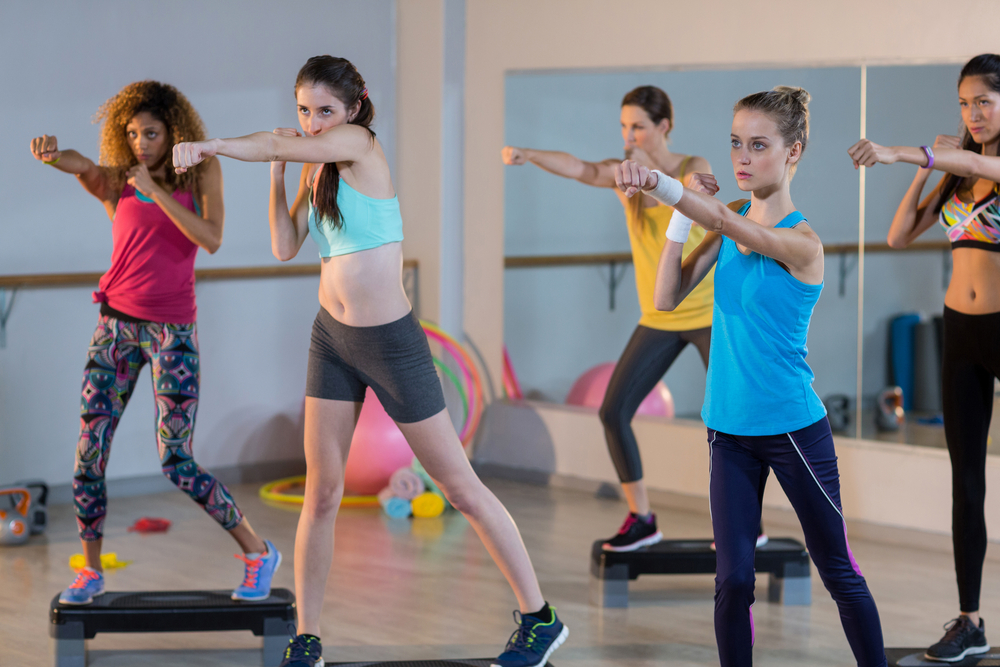 Group of women exercising on aerobic stepper in gym-1