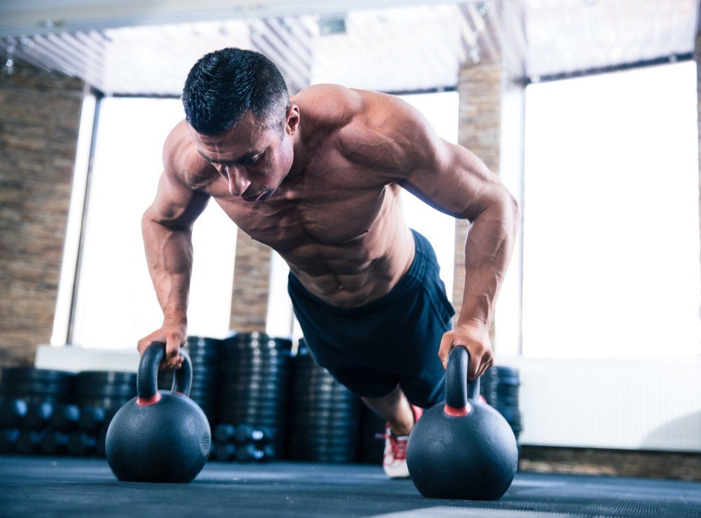 Handsome muscular man doing push ups on kettle ball in crossfit gym