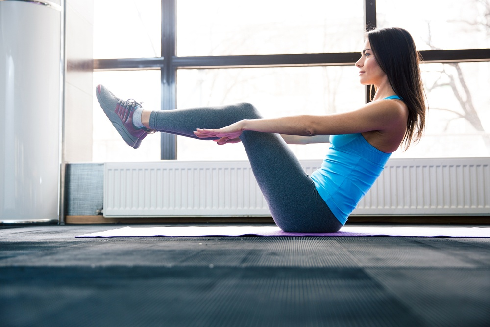 Happy young woman doing exercise on yoga mat at gym