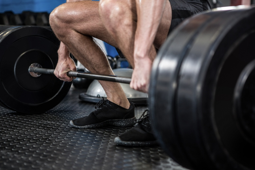 Low section of man lifting barbell in fitness studio