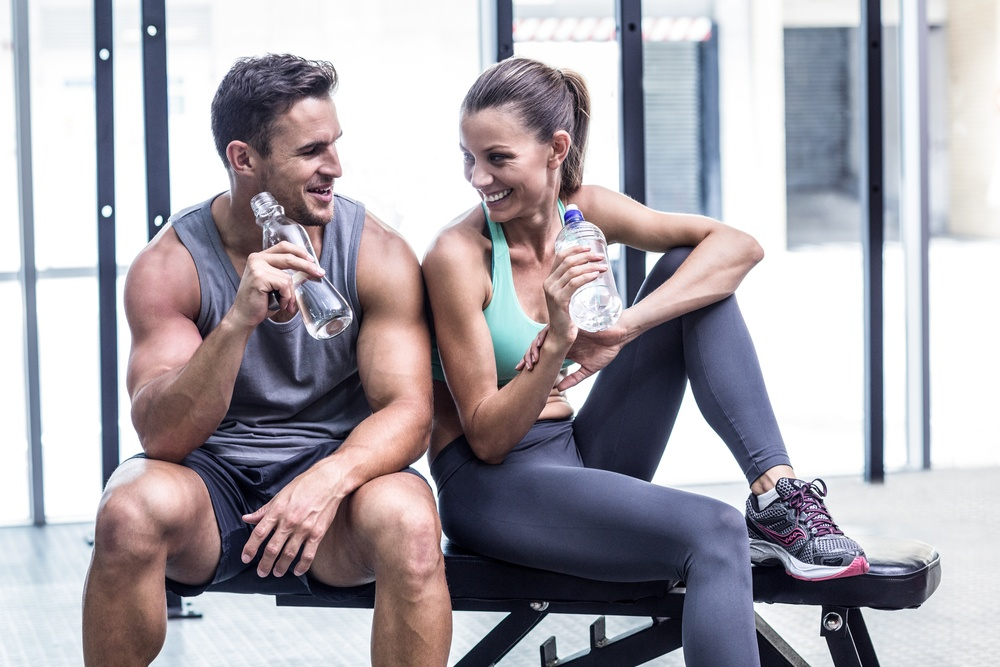 Muscular couple discussing on the bench and holding water bottle