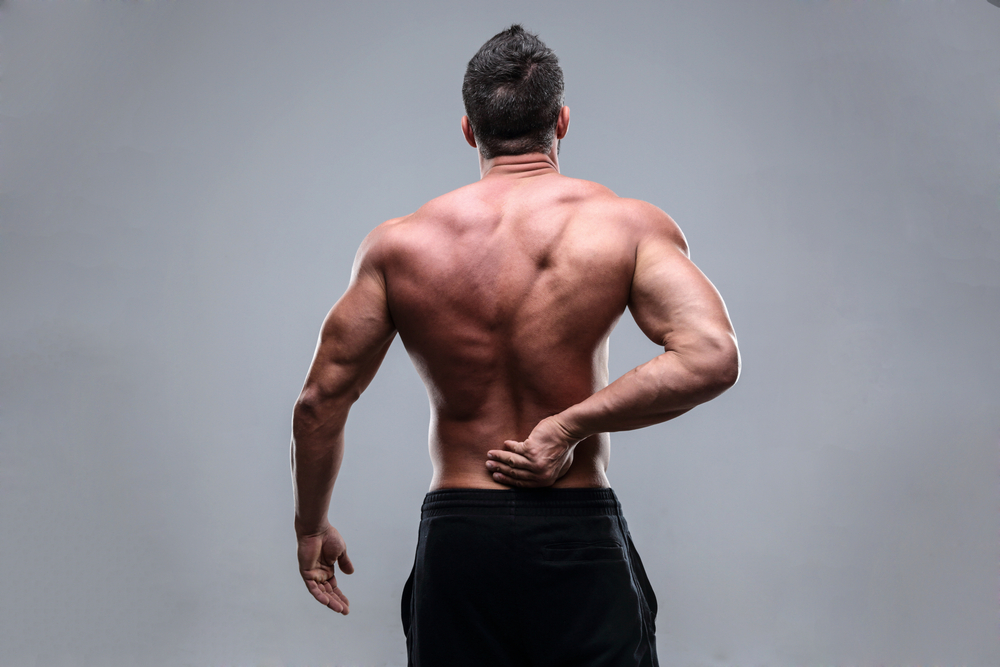 Muscular man with back pain on a gray background-1