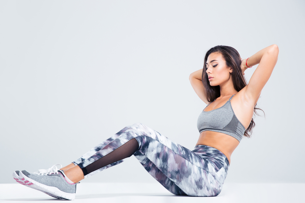 Portrait of a fitness woman doing abs exercises isolated on a white background-1