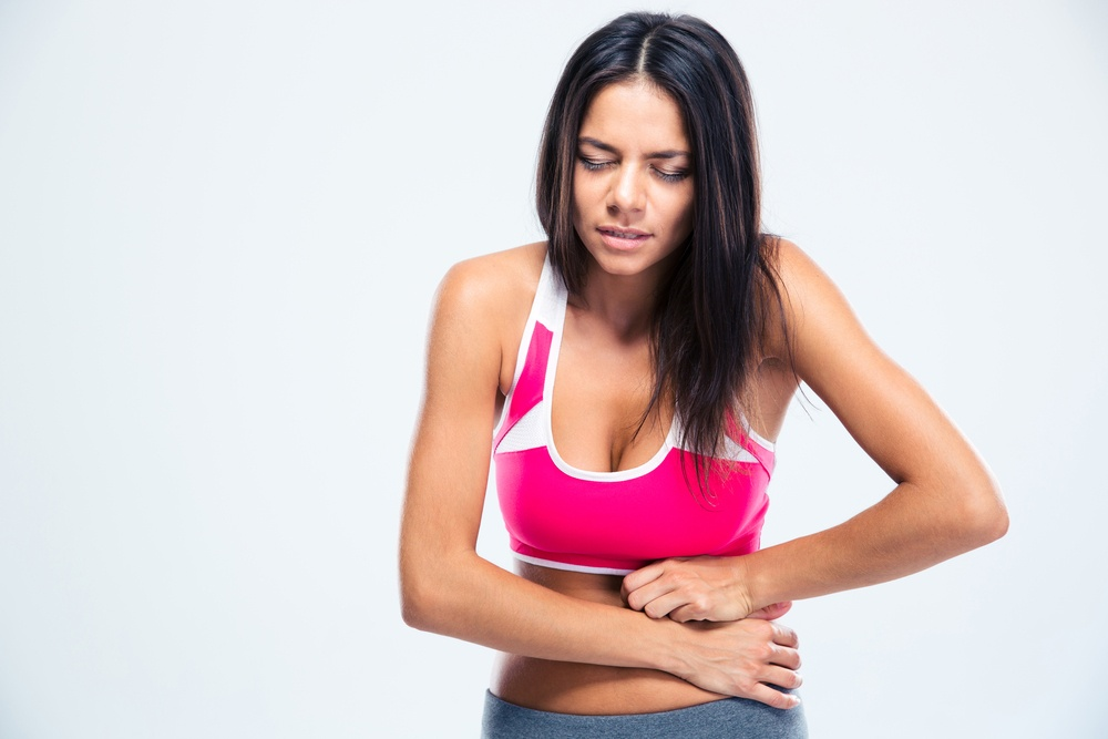 Portrait of a fitness woman with stomach pain over gray background-1