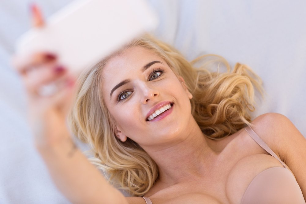 Portrait of a happy lovely woman making selfie photo on smartphone