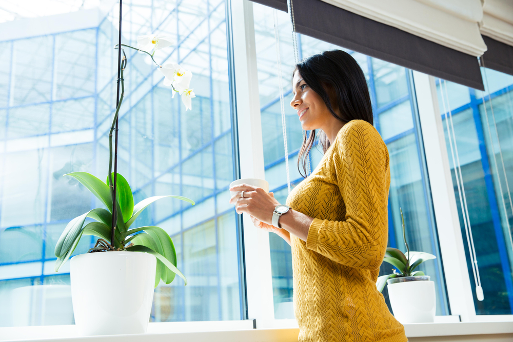 Portrait of a smiling businesswoman holding cup with coffee and looking at window in office