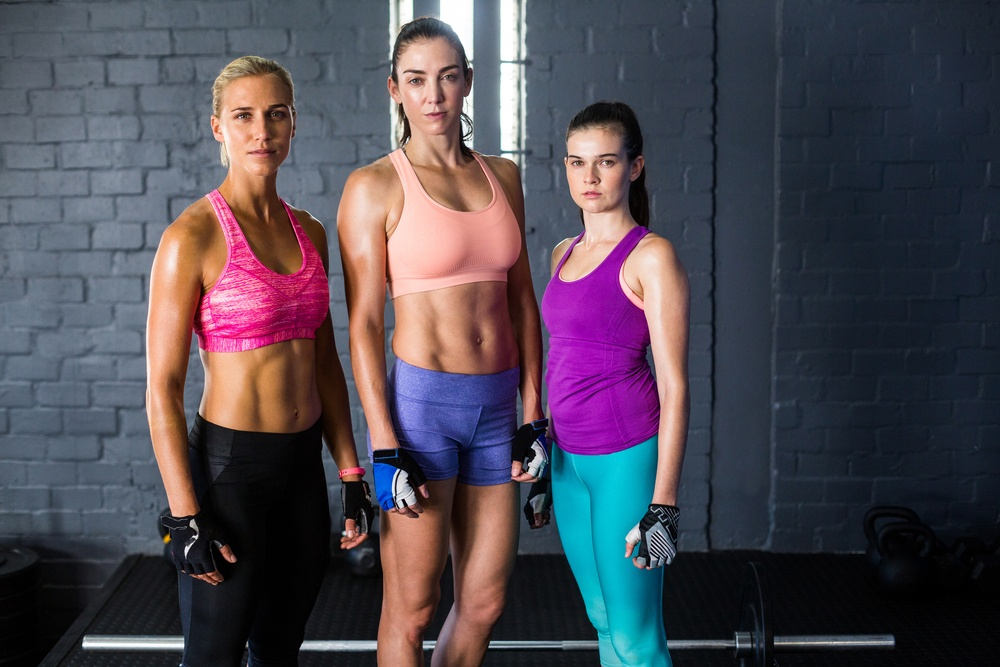 Portrait of female athletes standing against wall in gym