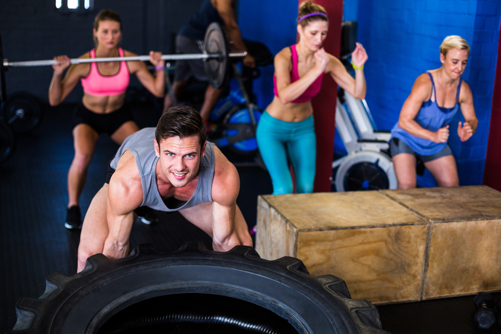 Portrait of smiling man lifting tire while exercising in gym-1