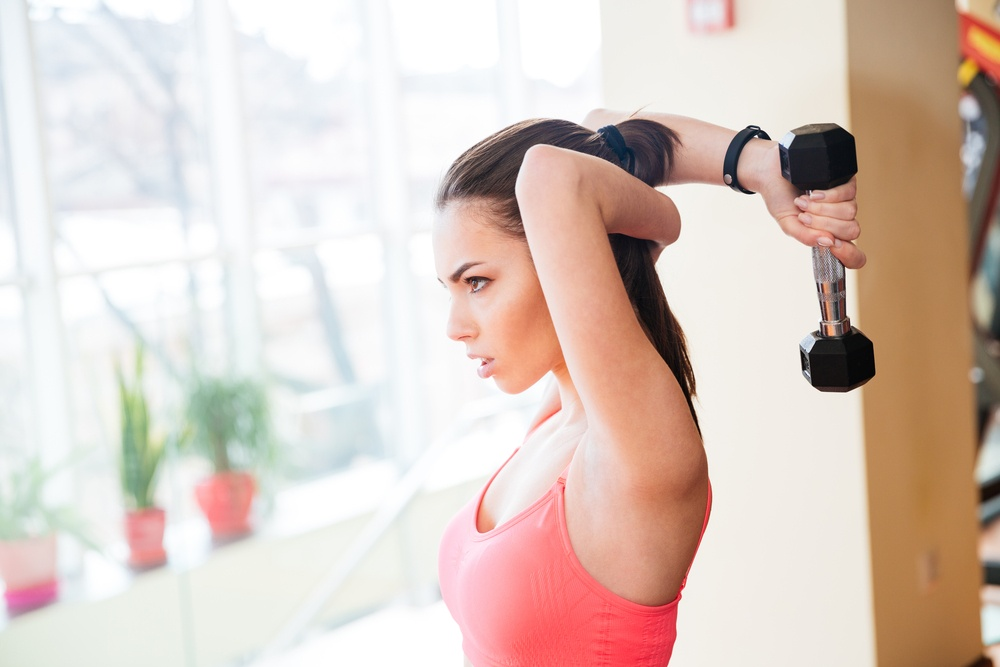 Profile of concentrated pretty young woman athlete doing fitness exercises with dumbbells in gym
