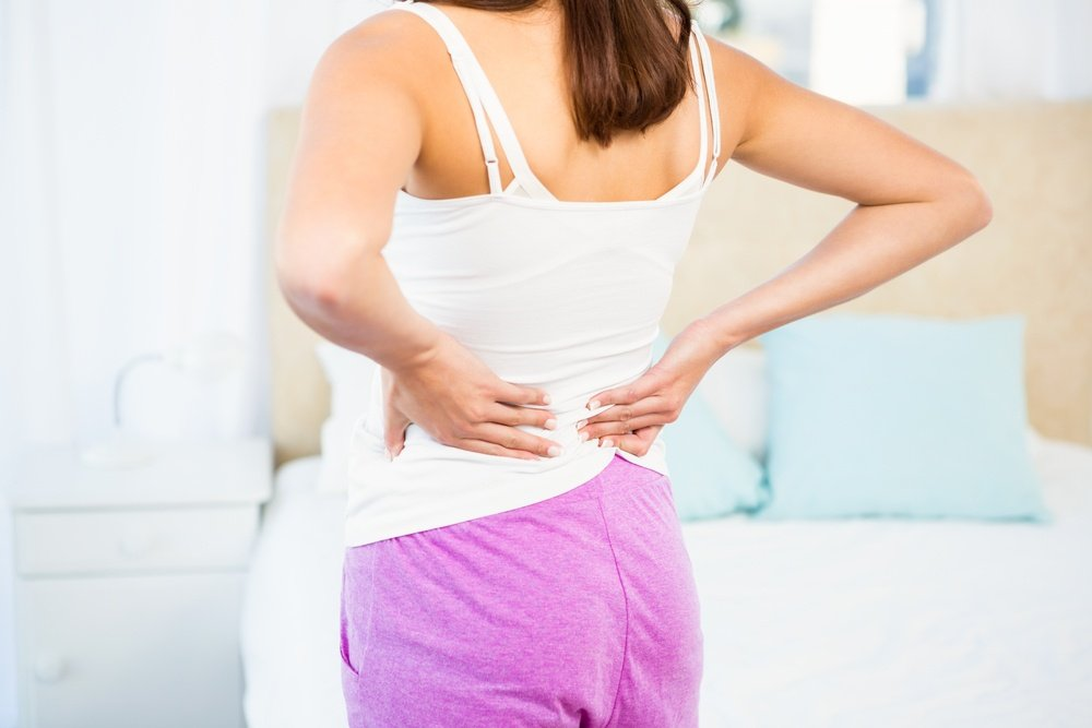 Rear view of a woman with back pain at home