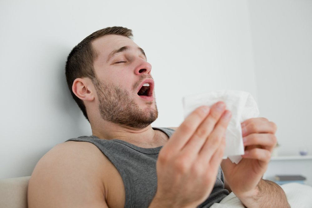 Sick man sneezing in his bedroom