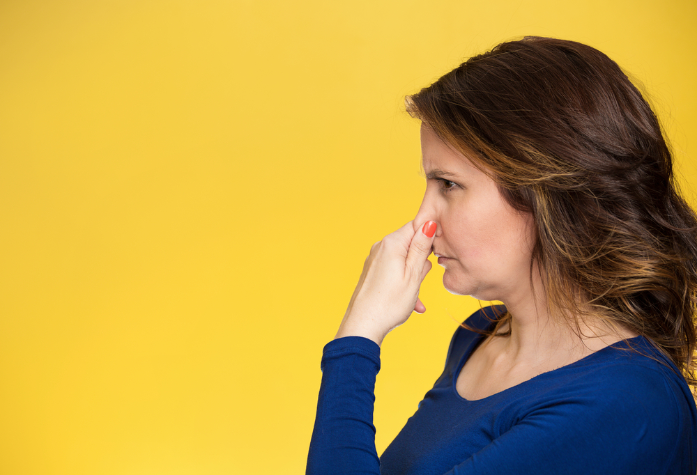 Side view profile portrait middle aged woman covers pinches her nose with hand looks with disgust, something stinks bad smell situation isolated yellow background. Human face expression body language-2