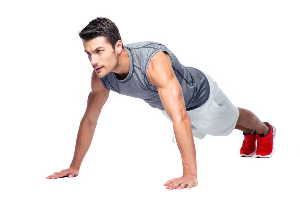 Sports man doing push ups isolated on a white background