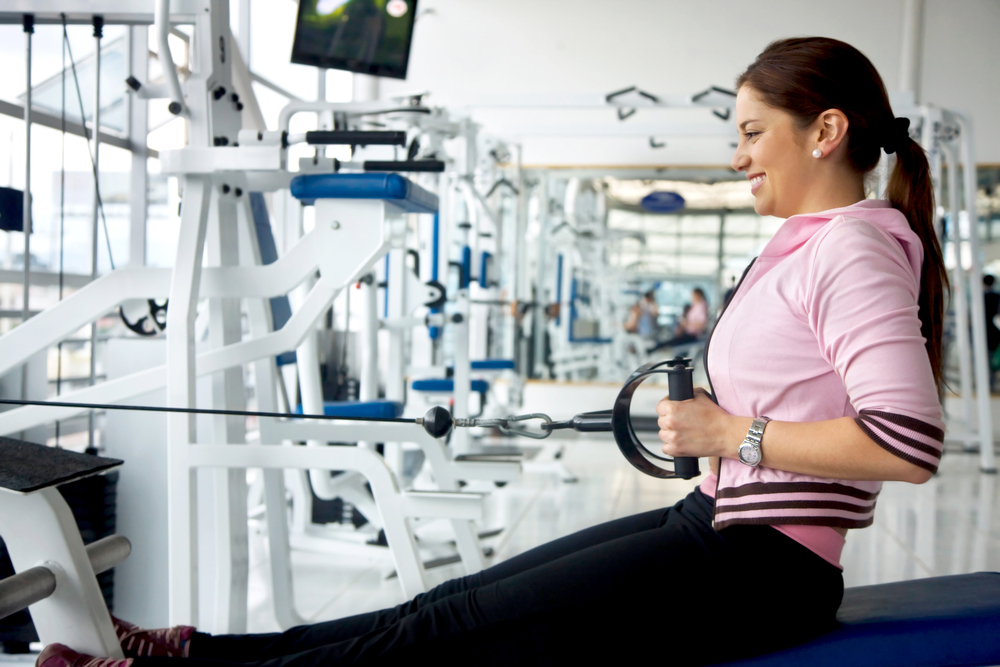 Strong gym woman exercising on a machine