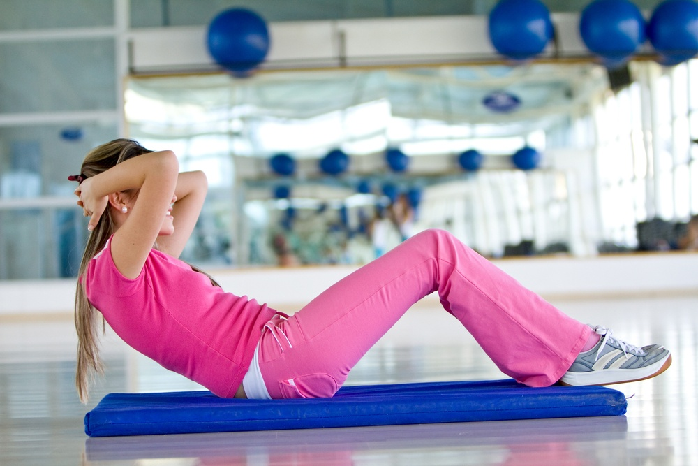 Woman at the gym doing exercises for her abs