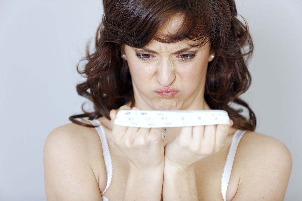 Woman looking angry at her tape measure after measuring her waistline.