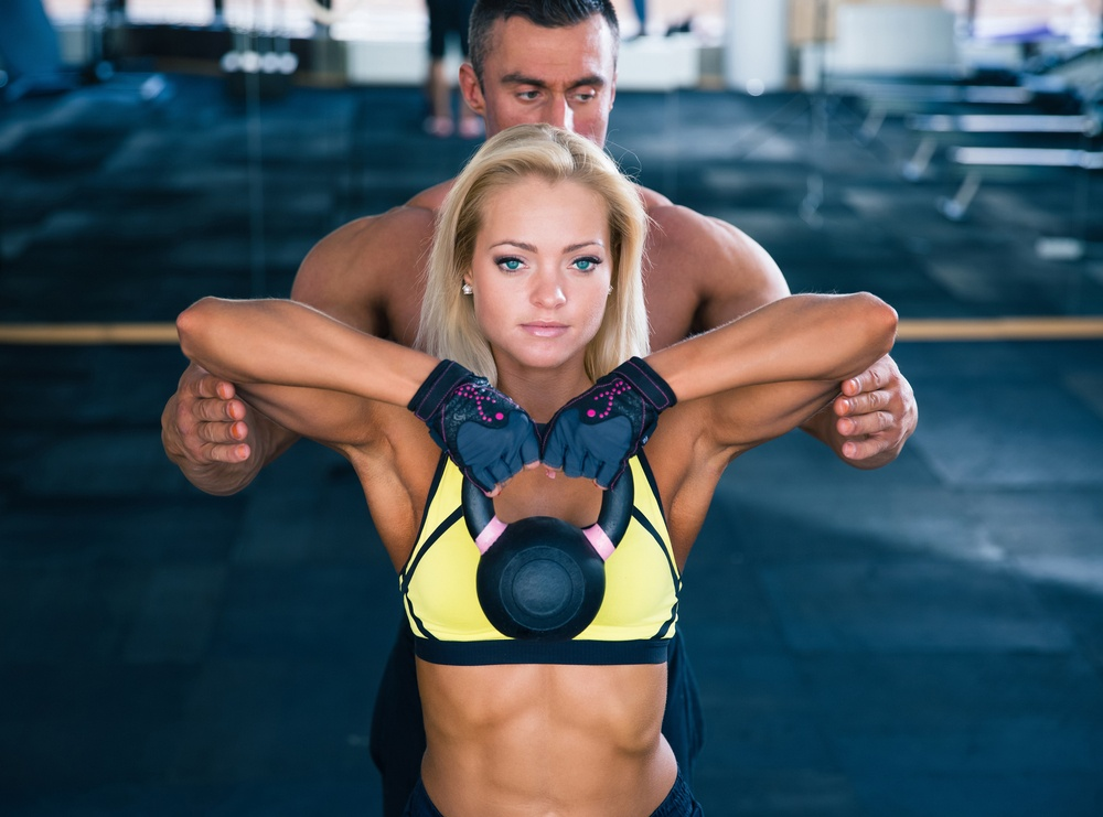 Woman workout with kettle ball and coach in gym-1