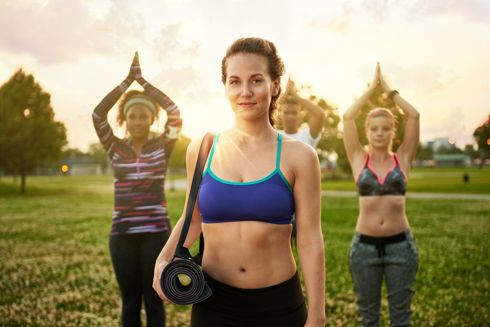 Young blond woman leading a yoga class at sunset in nature park