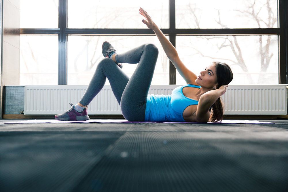 Young pretty woman lying on the yoga mat and doing exercise at gym